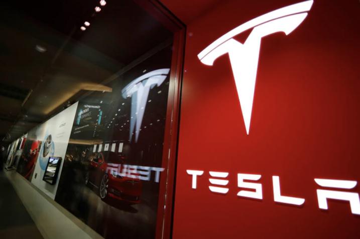 Obrazek przedstawia logo firmy Tesla, czyli producenta auta elektrycznego, o którym jest artykuł.