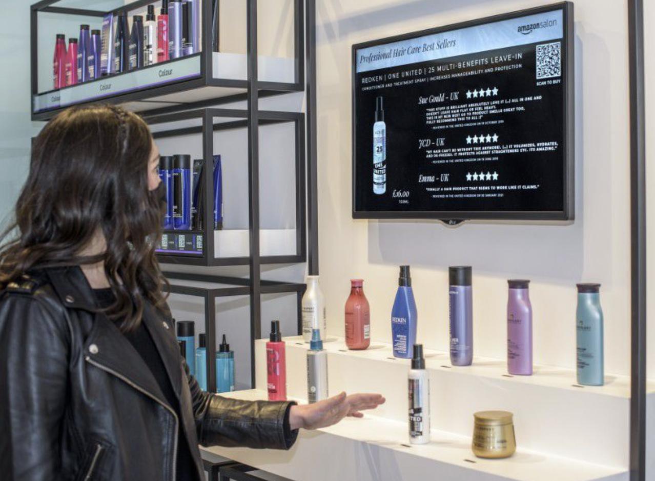 Obrazek pokazuje jak ma działać technologia point-and-learn. Widać na nim klientkę Amazon Salon, która wskazuje na kosmetyk a na ekranie wyświetlają się informacje na jego temat.