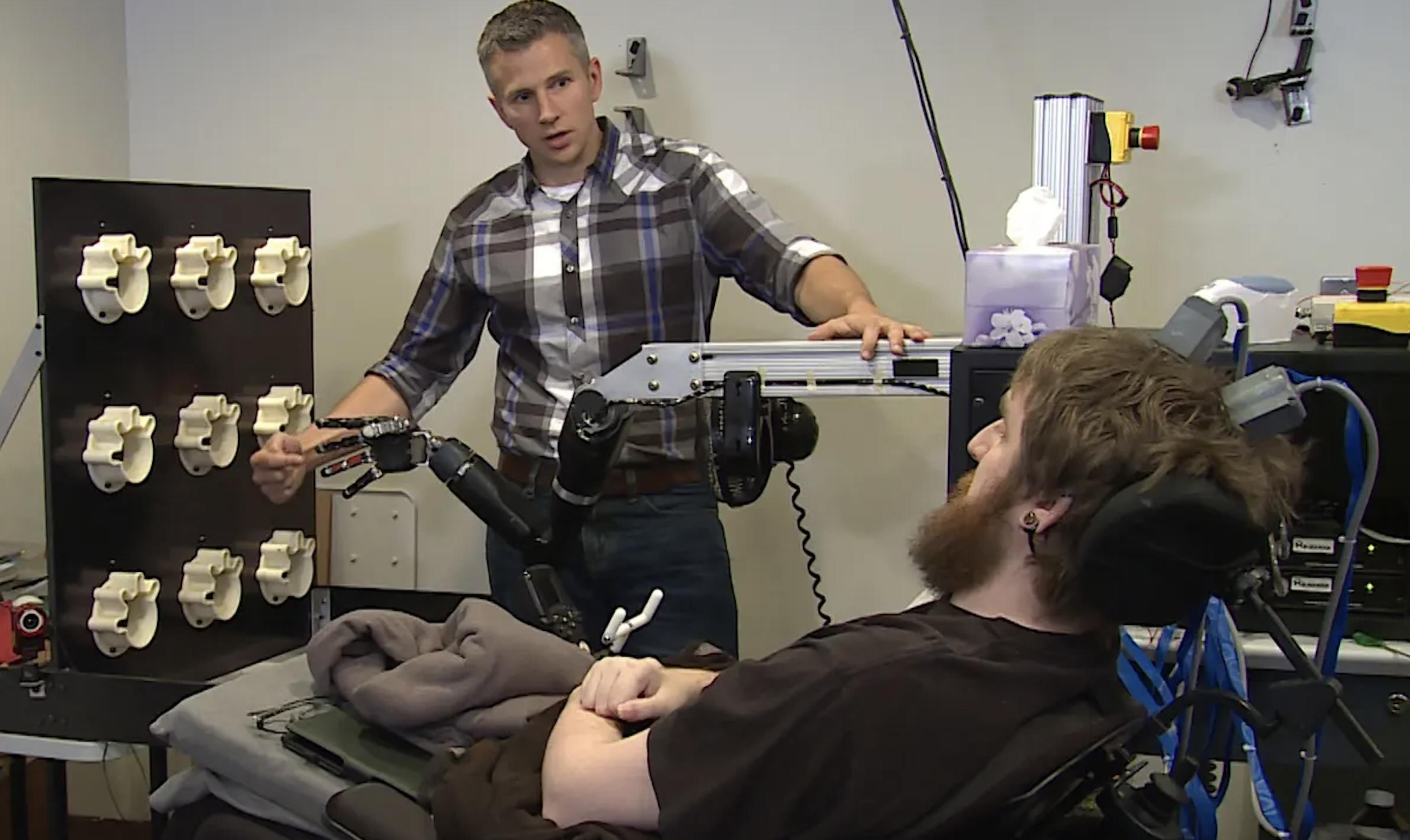 Obrazek pokazuje jak Nathan Copeland ćwiczy posługiwanie się protezą ręki.