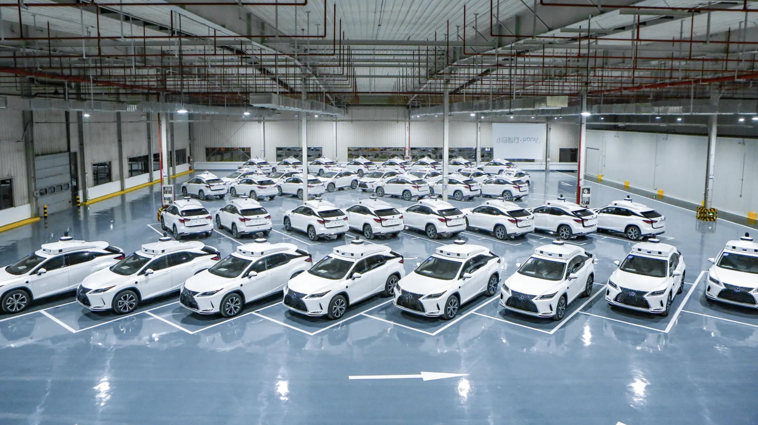 Obrazek przedstawia halę wypełnioną samochodami autonomicznymi typu robotaxi od firmy Pony.ai.